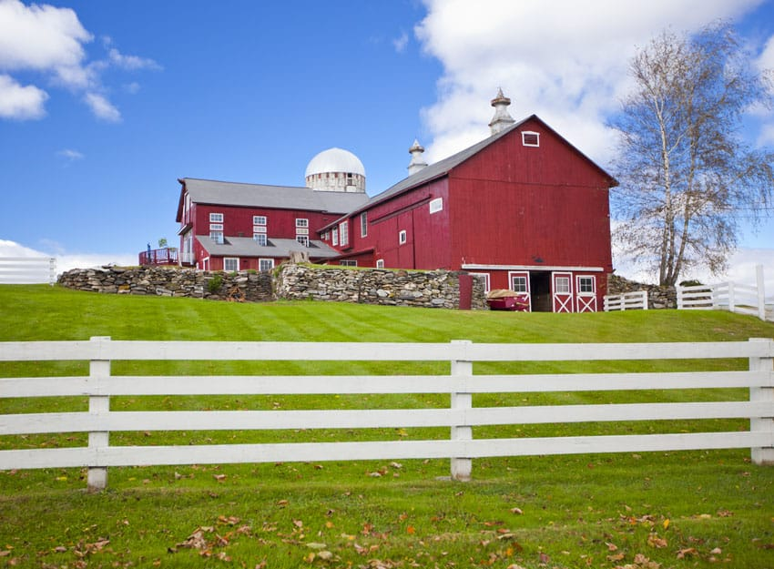 Traditional white farm fence with barn in background