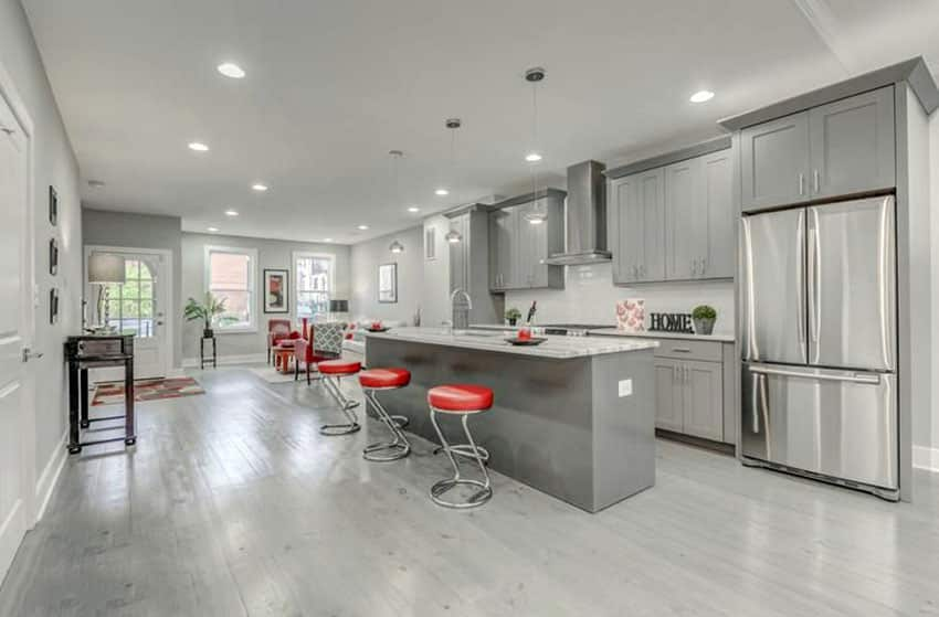 Transitional kitchen with gray cabinets and white marble countertops with breakfast bar island