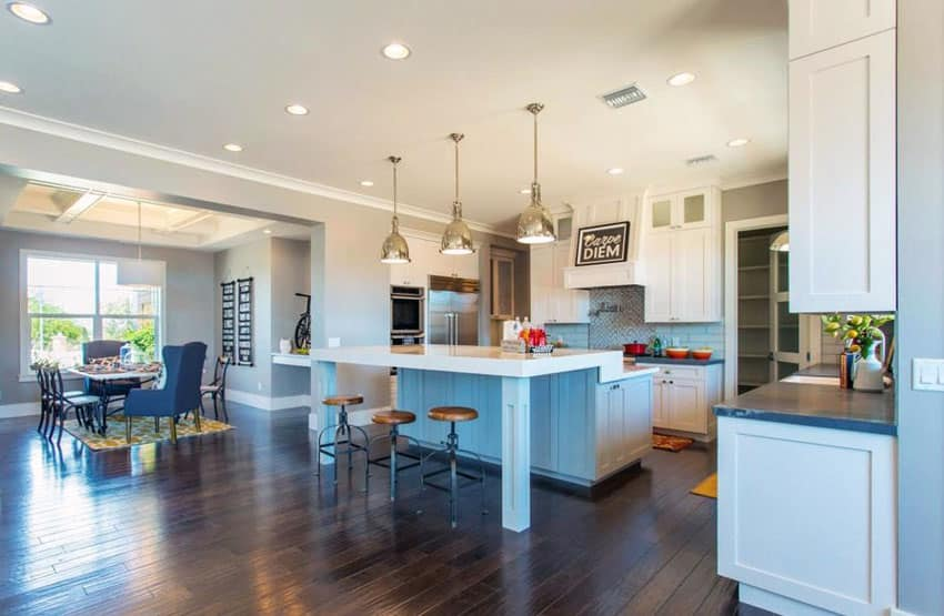 Transitional kitchen with light and dark quartz counters, blue two level island and white cabinets