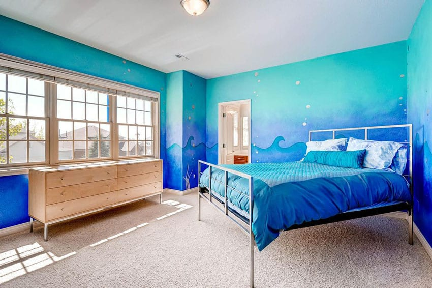 Tropical bedroom with blue painted walls with wave art design