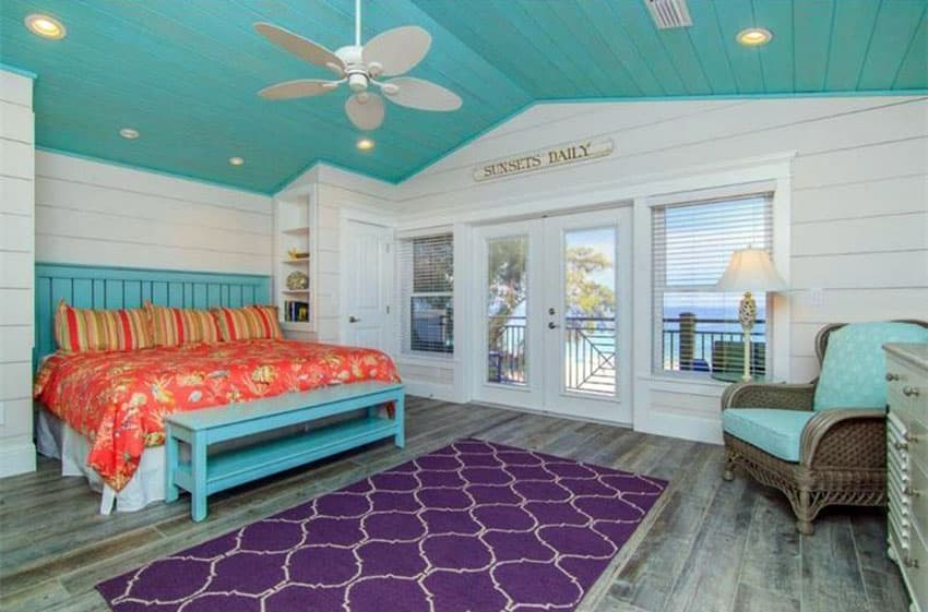 Tropical cottage bedroom with teal color ceiling and teal bed frame