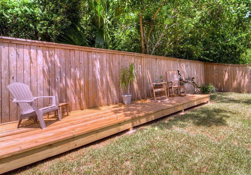 Vertical wood fence with raised deck in backyard