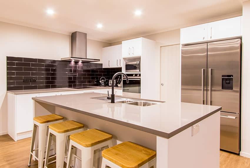 White cabinet modern kitchen with black brick backsplash and gray laminate counter island