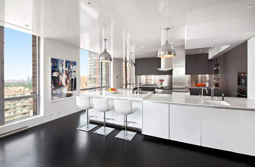 White modern cabinet kitchen with concrete floors and chrome pendant lights
