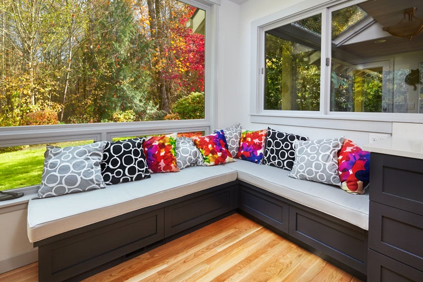 Window seat with large windows dark cabinet white cushions