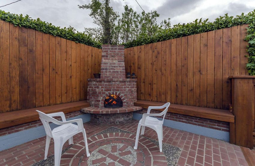 Wood fence surrounding backyard brick patio with fireplace