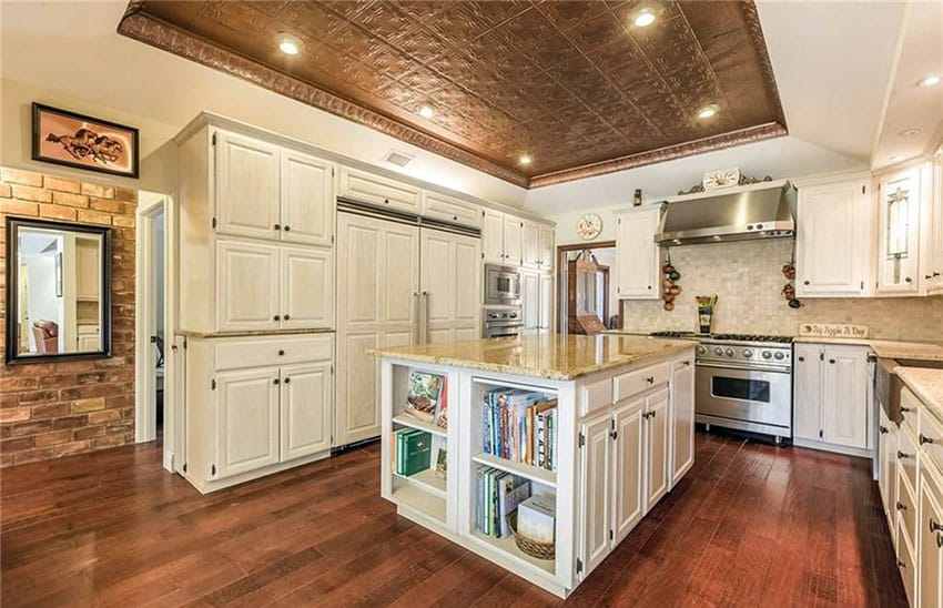 Kitchen with cream cabinets, integrated refrigerator, custom island and hardwood floors