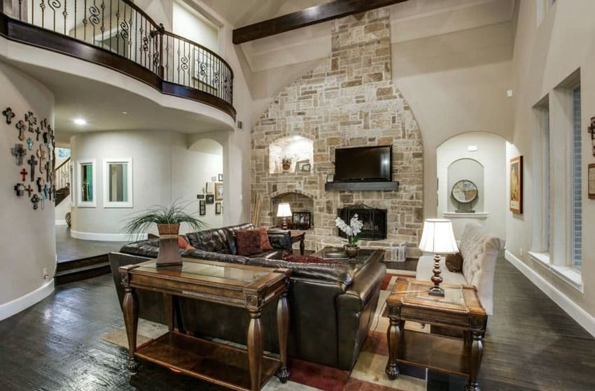 Mediterranean sunken living room with leather couch, dark wood floors and fireplace