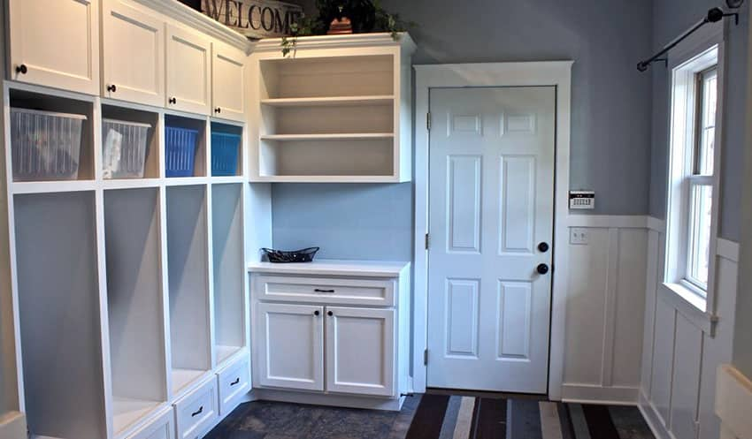 Mud room with white and blue theme wainscoting and built in cabinet