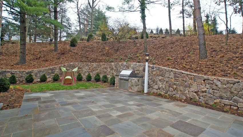 Contemporary flagstone patio with stacked stone retaining wall