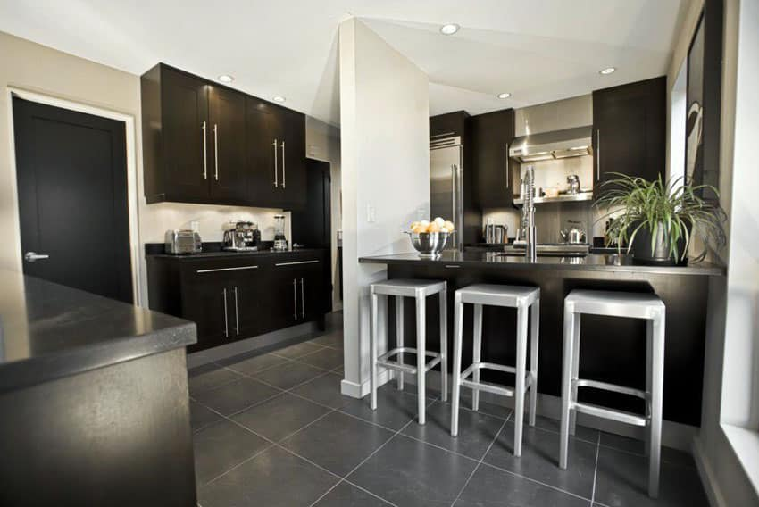 Contemporary kitchen with black cabinetry and gray porcelain floor tiles