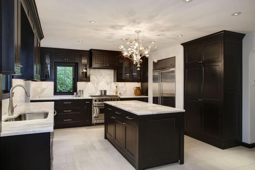 Contemporary kitchen with black cabinets, marble counter backsplash and chandelier