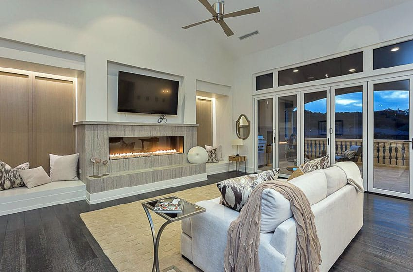 Contemporary living room with built in bench seating, gas fireplace and door to patio balcony