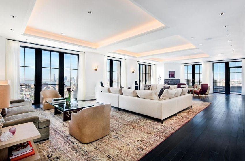 Contemporary living room with city views, wood flooring and tray ceiling with hidden accent lighting