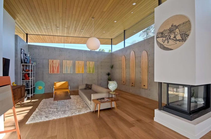 Contemporary living room with concrete walls wood flooring and high glass windows