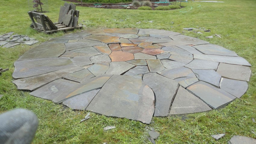 Cut stone patio circle in backyard surrounded by grass
