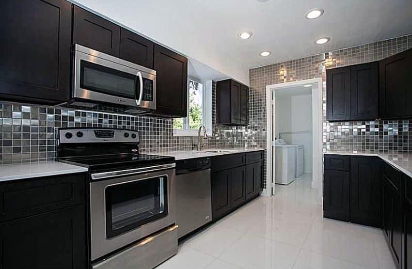 Dark cabinet kitchen with metallic backsplash