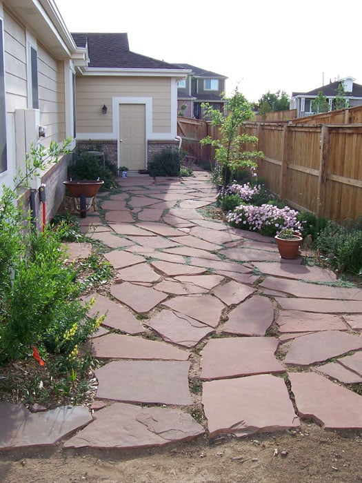 Flagstone patio in backyard with garden plants