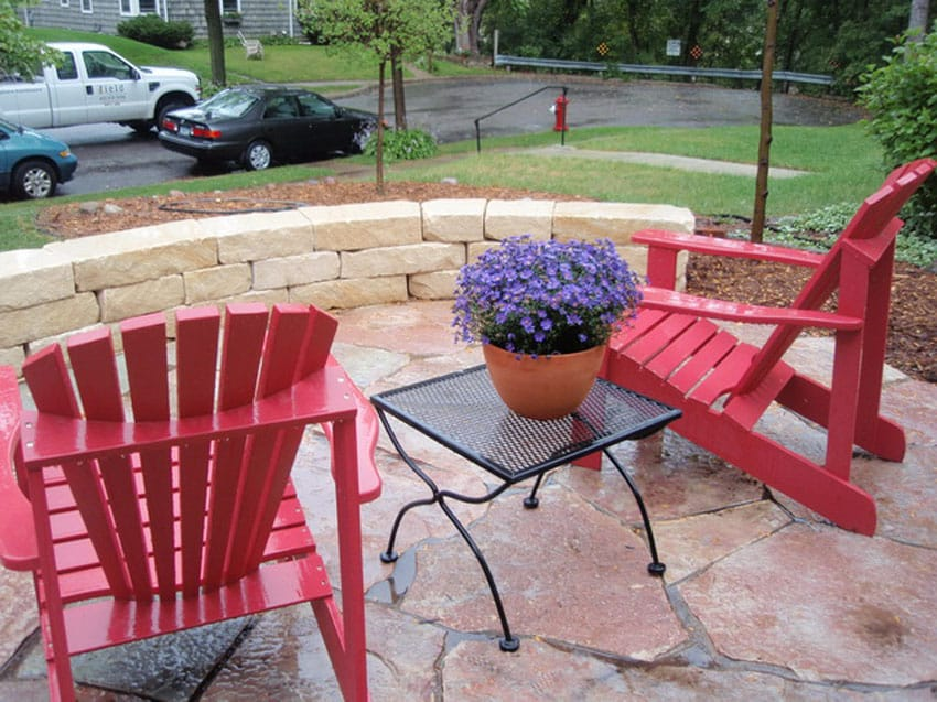 Flagstone patio with circular block wall and lounge chairs in front yard