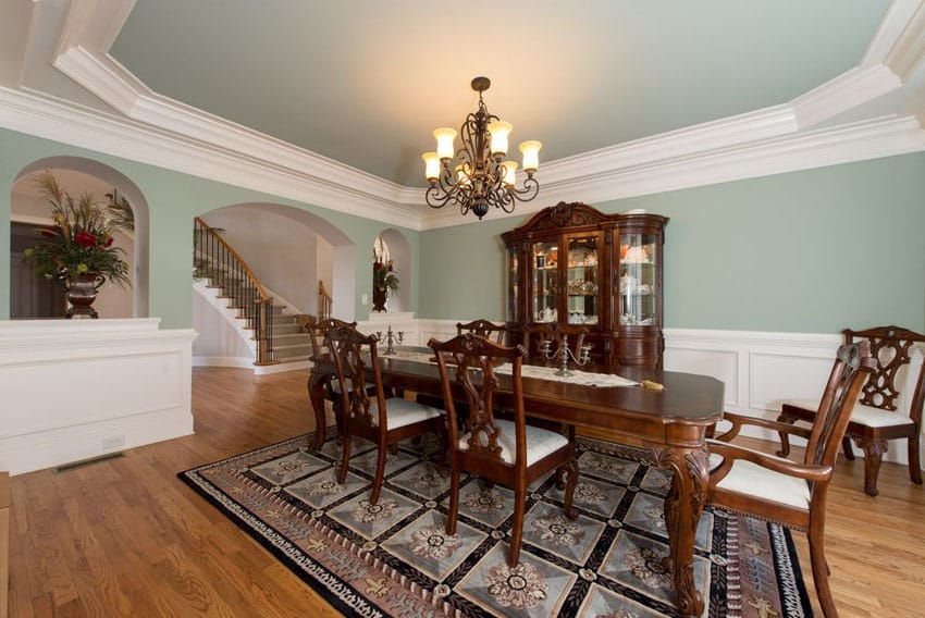 Green and white dining room with tray ceiling and wood floors