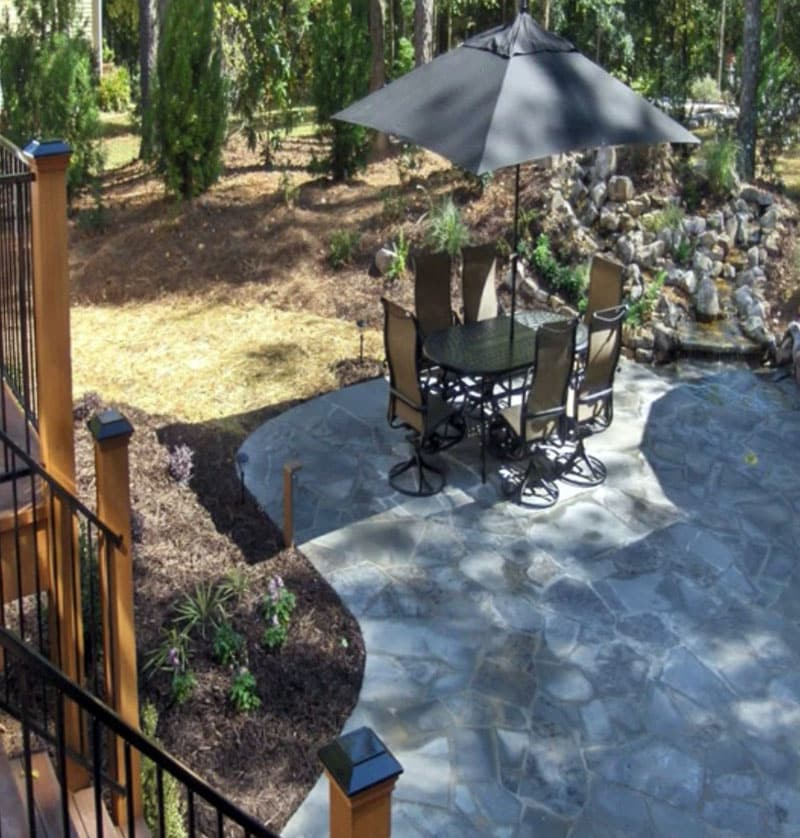 Irregular shaped stone patio next to deck