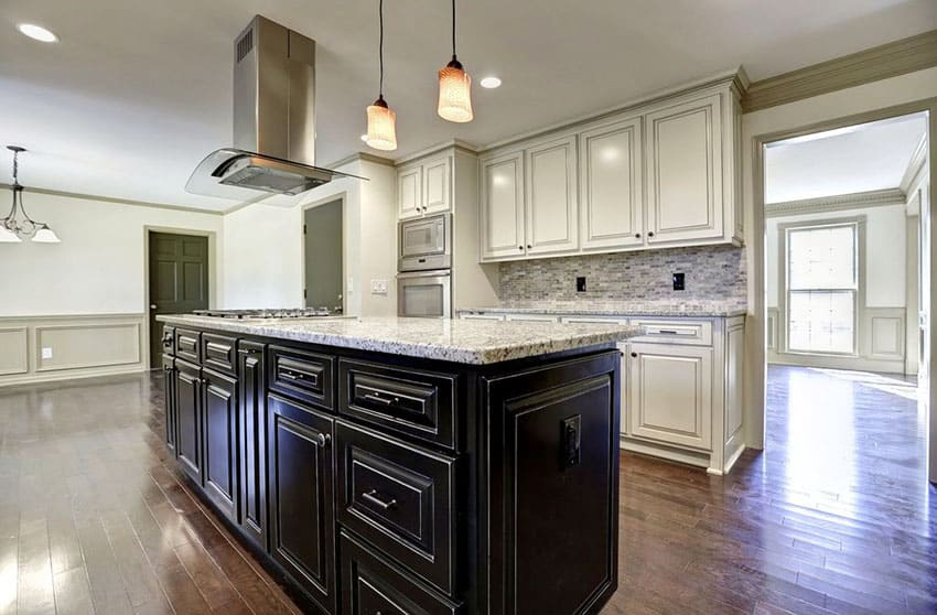 Kitchen with black cabinet island and white main cabinets with white granite countertops