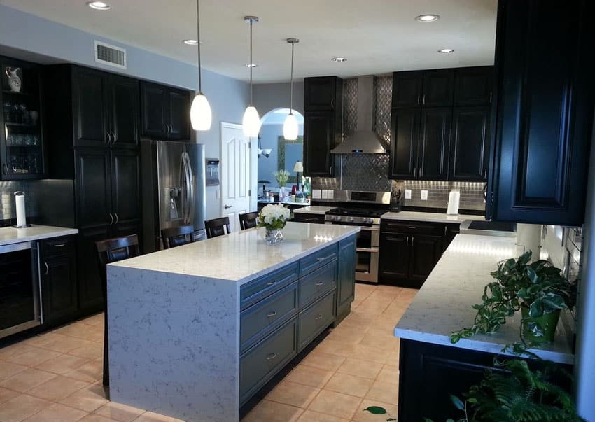 Kitchen with black cabinets white counter island and stainless steel backsplash