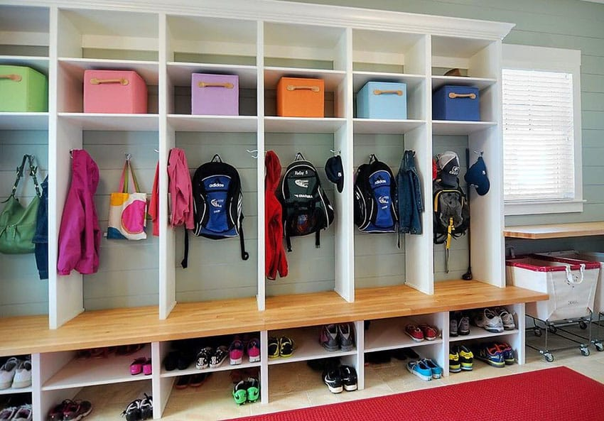Large mudroom with clothing hangers shoe cubbies and wood bench
