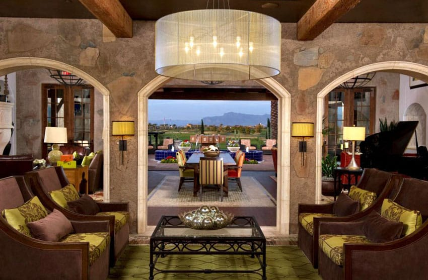 Living room with brown furniture and archways to outdoor patio