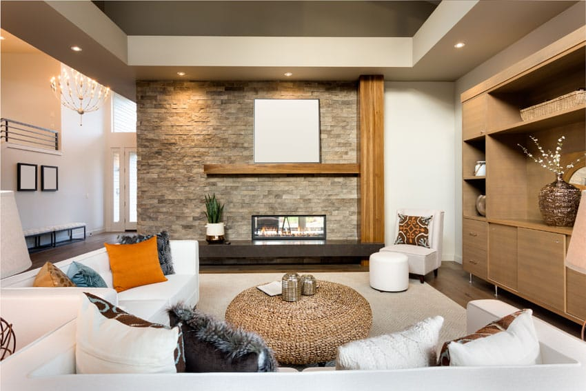 Living room with stacked stone fireplace and built in bookshelves