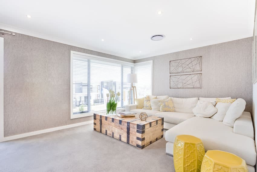 Living room with white sectional sofa, rustic wood chest coffee table and yellow end tables