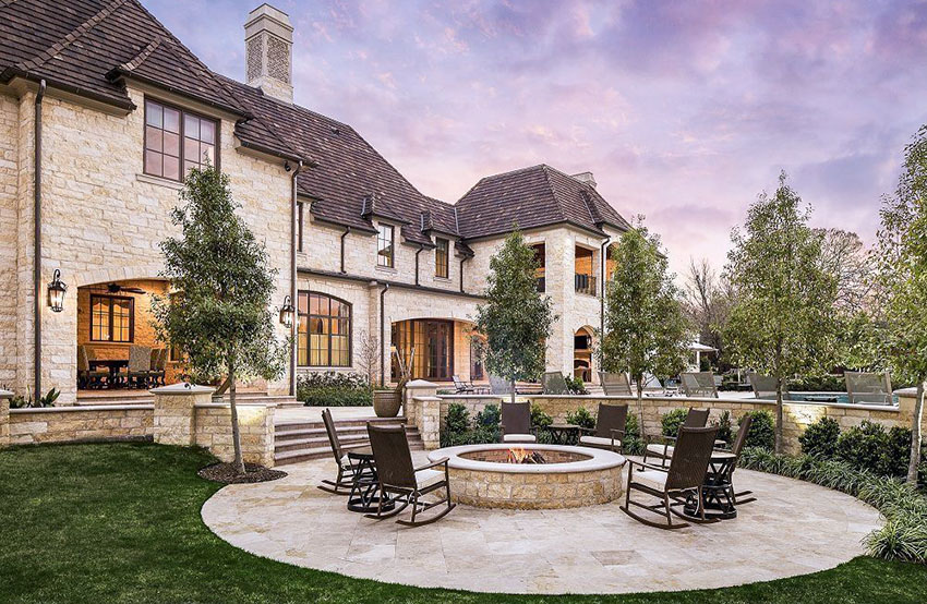Luxury home backyard patio with round design and center stone fire pit
