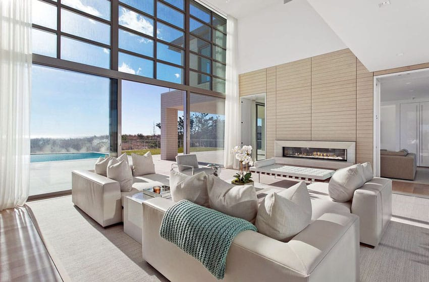 Luxury living room with comfortable furniture and large window view of the swimming pool