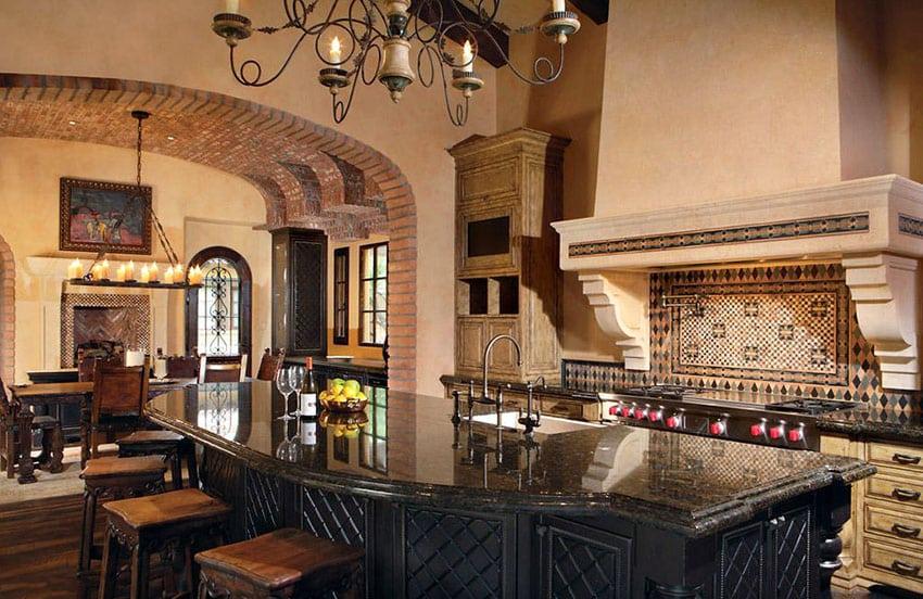 Mediterranean kitchen with dark gray granite island and rustic tile backsplash