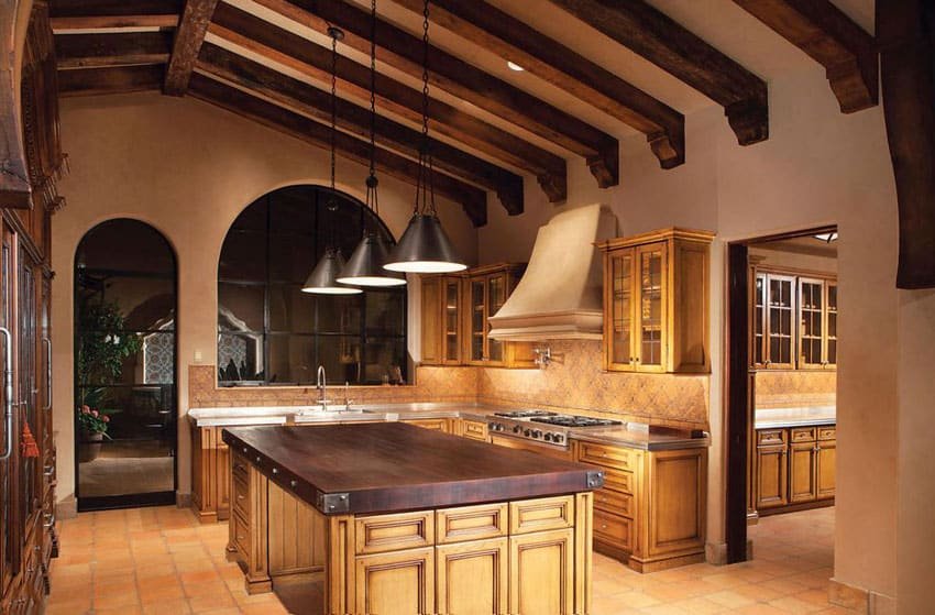 Mediterranean kitchen with high open beam ceiling and solid wood countertop island