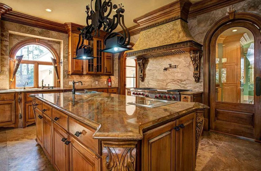 Mediterranean kitchen with light brown granite counter and custom cabinetry