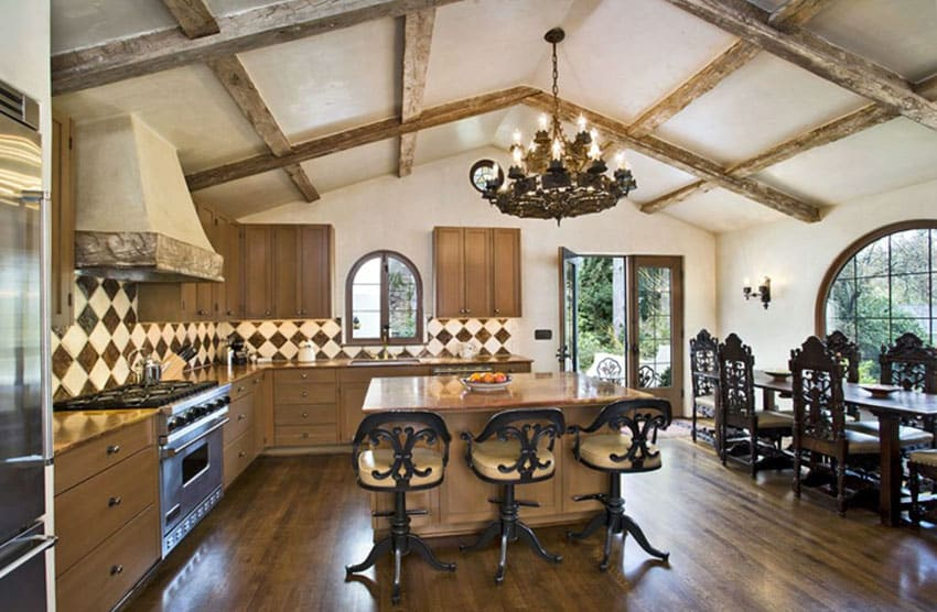 Mediterranean kitchen with rosewood granite countertops and wood beam cathedral ceiling