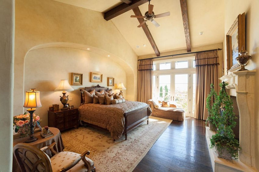 Mediterranean style bedroom with tan painted walls exposed beam vaulted ceiling and fireplace