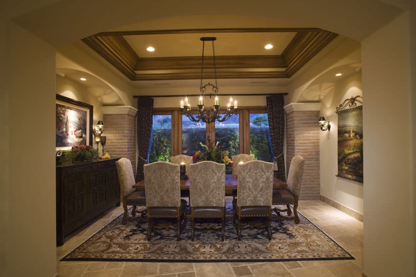 Mediterranean style formal dining room with tray ceiling and patio views