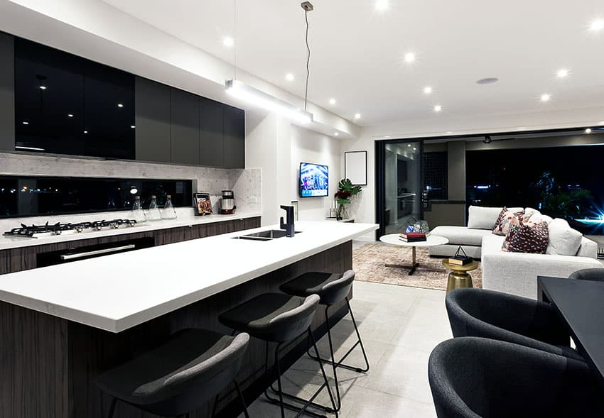 Modern kitchen with black cabinets white counters and breakfast bar