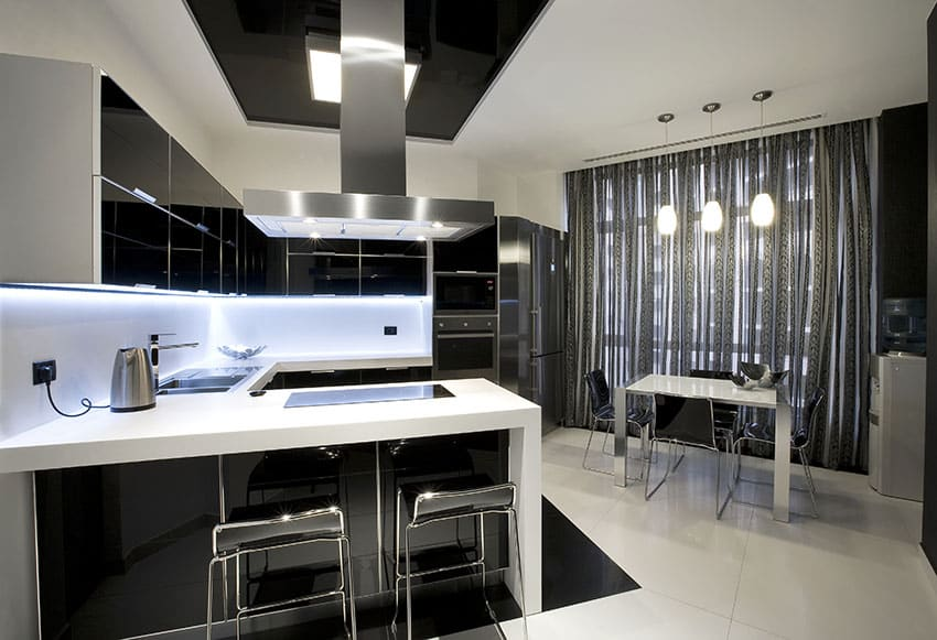 Modern kitchen with black high gloss cabinets white counters and dining peninsula