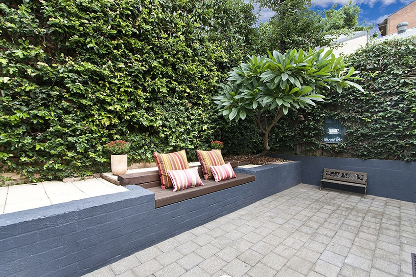 Paver patio with rustic wood bench and hedges in backyard