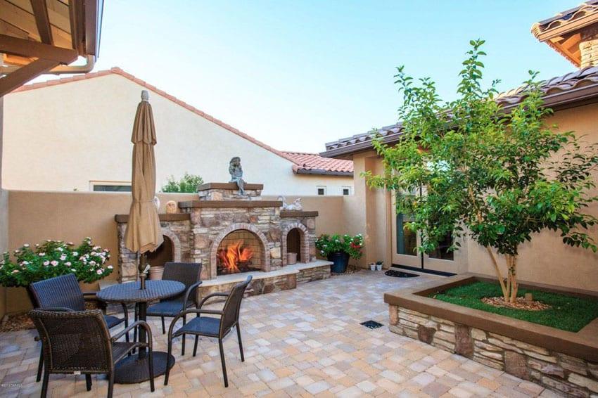 Paver stone patio with backyard fireplace