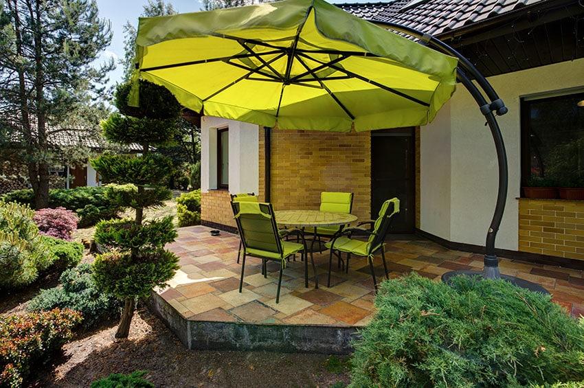 Raised slate patio in backyard with large umbrella shade
