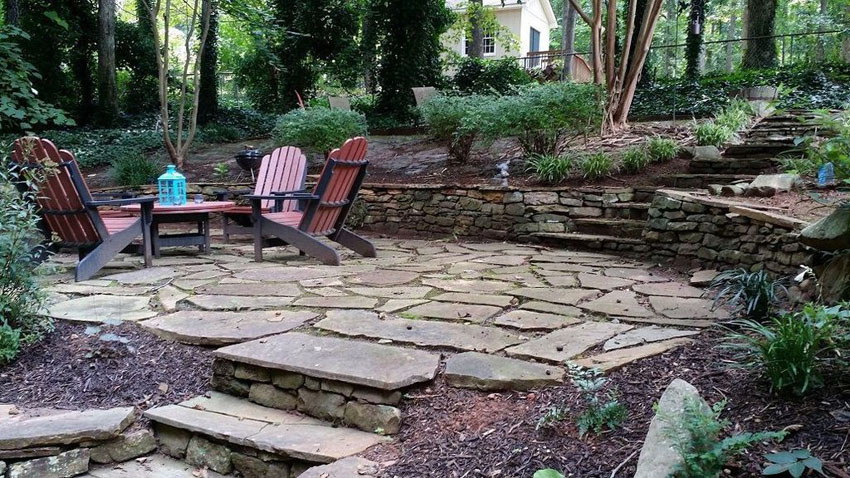 Rustic cut stone backyard patio with stone steps