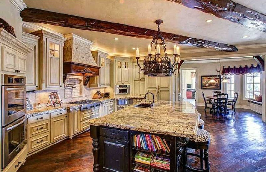 Rustic kitchen with raised panel cabinets dark wood island and gothic chandelier