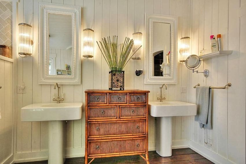 Small bathroom with central wood storage cabinet between two sinks