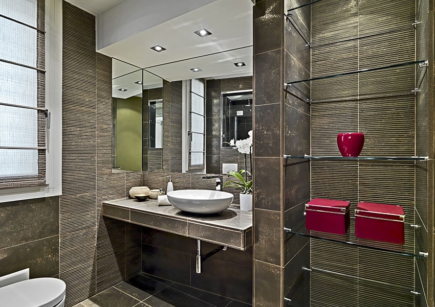 Small bathroom with dark brown tile and glass shelving