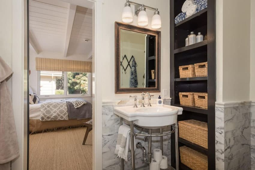 Small bathroom with pedestal sink and built in storage shelving with wicker baskets
