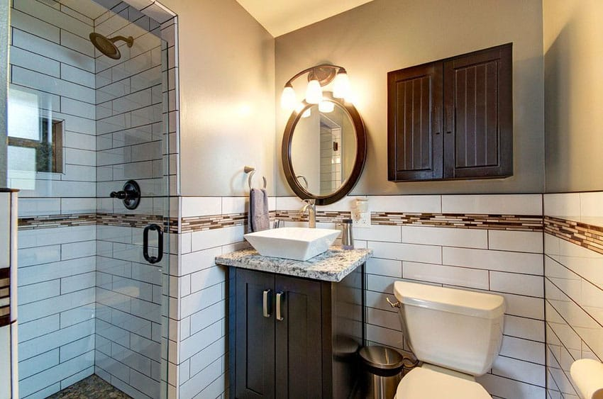 Small bathroom with subway tile and wood cupboard